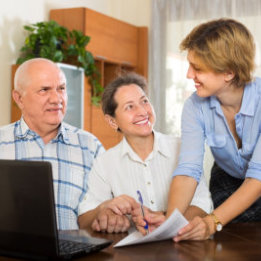 Smiling senior couple answer questions of social worker at home