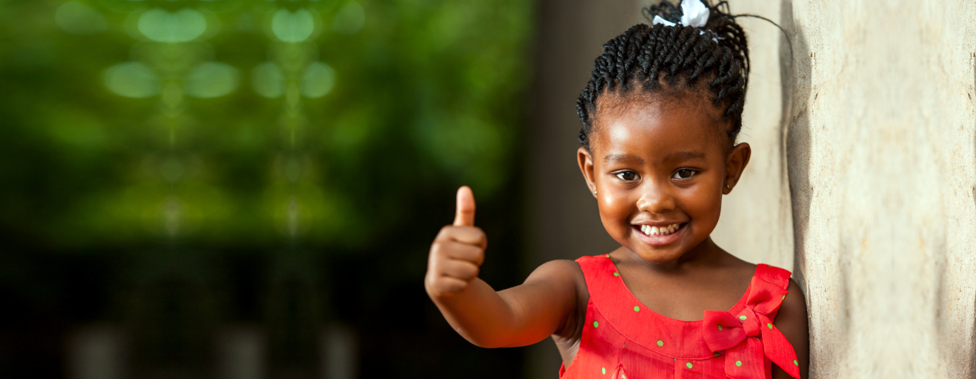 Portrait of happy little african girl doing thumbs up sign